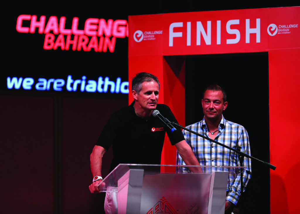 BAHRAIN, BAHRAIN - DECEMBER 06: Zibi Szlufcik (left) and Felix Walchshšfer (right) of Challenge Family speak at the awards presentation after the Challenge Triathlon Bahrain on December 06, 2014 in Bahrain, Bahrain. (Photo by Stephen Pond/Getty Images for Challenge Triathlon)